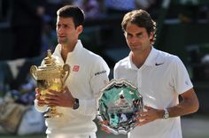 Novak Djokovic and Roger Federer with their winning trophies at the 2014 Wimbledon Final.