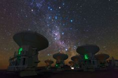 """Antennas of the Atacama Large millimeter/submillimeter Array. This shows the constellations of Carina (The Keel), Vela (The Sails), and the Milky Way. The bright orange star is Suhail in Vela, the similarly orange star in the upper middle is Avior, in Carina. Of the three bright blue stars that form an """"L"""" near these stars, the left two belong to Vela, and the right one to Carina. And exactly in the centre of the image below these stars gleams the pink glow of the Carina Nebula (eso1208),"""""""