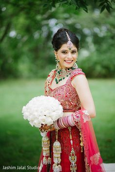 This Indian bride poses for lovely wedding portraits in a beautiful red lengha.