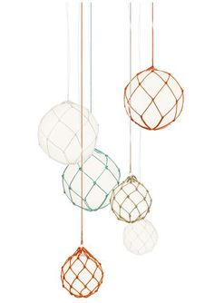 Fisherman pendant, Modeled after classic glass maritime floats, the Fisherman Pendant is made of polypropylene globes suspended in hand-knitted nets made in Hönö on the west coast of Sweden. Designed by Matthias Stahlbom for Swedish lighting company Zero; discovered via Dezeen.