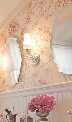 Love the beveled mirrors, ceiling, sconce, beadboard and the idea of using wallpaper in a bathroom...