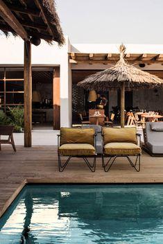 Un plancher en bois, une pergola naturelle et des fauteuils douillets réchauffent la plage de cette piscine bleutée