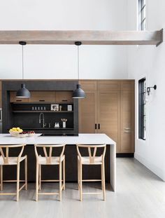 Tan wishbone counter stools sit at a black kitchen island positioned a white quartz waterfall counte Hamptons House, The Hamptons, Kitchen With High Ceilings, Black Kitchen Island, Kitchen Islands, Waterfall Countertop, Chic Beach House, New England Farmhouse, Quartz Kitchen Countertops