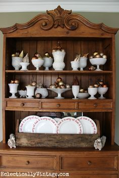 A beautiful display of milk glass vases and other containers filled with vintage gold-colored Christmas ornaments.  Simple, but striking.