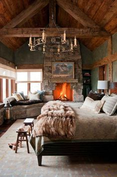 Chic, rustic and cozy cabin bedroom with dramatic chandelier, fur blanket, and wood paneled walls.