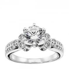 Timeless in its ornate architectural beauty, the Westminster Abbey ring gets even more lovely the closer you look. The  Contemporary Nexus Diamond™ center stone is surrounded by six accents enclosed in millgraine bezel settings, supported by arched profiles reminiscent of flying buttresses. The band is etched with relief detailing and fine metalwork, completing the structural elegant look.  Center stone is available in a variety of carat weights; choose yours from the menu above. Six Round…