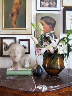 Table and paintings. Marble, brass, lilies, candle, books...