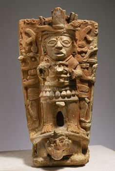Censer Support, 8th–9th century  Mexico; Maya/This hand-modeled flanged ceramic cylinder would have supported a bowl for the burning of incense for ritual purposes. A high-relief standing figure with a looped motif between his eyes, which is thought to relate to the Maya god of the sun, is depicted on the front.
