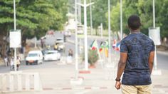 man - road - roundabout - crossroads - lampposts - flags - public place - traffic - motorcycles - cars - drivers - people - trees
