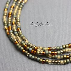 A multi-color gold tone glass seed bead necklace. Colors include metallic gold, frosted gold, sandstone, metallic copper, and tans. These are 8/0, glass seed beads. The necklace could be layered with