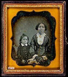 African-American woman, child. Woman wearing brooch, earrings, necklace, rings, mitts, closed fan. Gold; brooch, earrings.