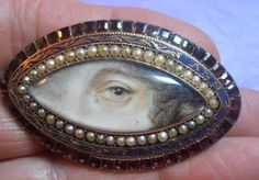 FINE RARE GEORGIAN DOUBLE LOVERS EYE MINIATURE ONE WITH TEAR BOTH LADIES NAMED. The front has a dark blue enamelled border with the name Ann Colgrave to the right hand side surrounded with a line of seed pearls and a border of flat square cut garnets. The reverse is engraved and has the name Emma Maria Cooke in script to the edge. Sold for £1.600,00 Ca. EUR 1.946,99