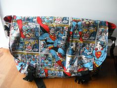 """Handmade Superman Messenger bag/Purse.  Fabric--exterior is 100% cotton, interior is durable duck canvas.  Measures approximately 14"""" w 10"""" h. Features--3 organizer pockets under flap, 1 interior pocket with velcro closure, adjustable Nylon strap, and 2 parachute buckles to keep purse closed securely.  If you are interested in purchasing visit my esty shop"""