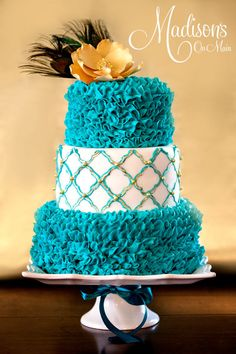 The top and bottom tier I piped teal buttercream ruffles.  The middle tier is covered with fondant, then I stenciled it with a teal quatrefoil pattern.  Then I painted over that with gold highlighter dust mixed with vodka.  I placed a gold hand made gumpaste flower on top, and in the center of the flower is...
