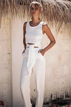 The Waist Tie Jumpsuit features a soft, cotton marl top with a round neckline and a classic singlet top fit with a cutout at the waist. The pants are made from super soft fabric and feature twin side pockets, fitted straight legs and a tie feature at the front. Pull on style. By SABO LUXE.