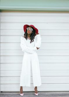 Kokabuta wears Winter Whites perfectly in our white pleated wide-leg crop pants paired with a cozy sweater. She adds some color to this look with a vibrant red hat and red and white printed pumps | Banana Republic
