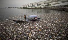 Um pequeno barco recolhe lixo na Baía de Guanabara, na Praça Mauá, ao lado do Museu do Amanhã, no Rio de Janeiro Foto: Márcia Foletto / Agência O Globo