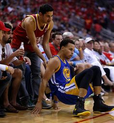 Description of . Golden State Warriors\' Stephen Curry (30) is helped up by Houston Rockets fan in the second quarter of Game 3 of the NBA Western Conference finals at the Toyota Center in Houston, Texas, on Saturday, May 23, 2015. (Nhat V. Meyer/Bay Area News Group)