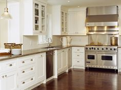 kitchens - creamy white kitchen cabinets glass-front cabinets granite stainless steel appliances off-white subway tiles glass pendant  Beautiful