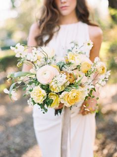romantic blush and butter ranunculus bouquet with dogwood by Studio Mondine