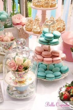 Tea party vignette. Floral arrangement in a tea cup under a dome. Pink and blue macarons. Cupcakes.