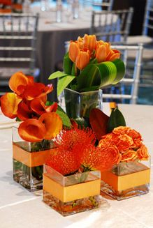 The company used square glass vases filled with orange tulips, roses, and calla lilies and red pincushions accented with orange ribbon and magnolia leaves as centerpieces at the MorseLife Geriatric Symposium in West Palm Beach. Tropical Centerpieces, Table Centerpieces, Wedding Centerpieces, Table Decorations, Centrepieces, Orange Wedding, Floral Wedding, Wedding Flowers, Orange Party