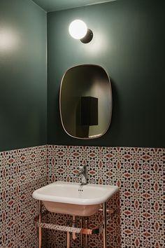 O revestimento em azulejos coloridos torna as paredes do banheiro equilibradas, juntamente com um espelho vintage e um lavatório branco.
