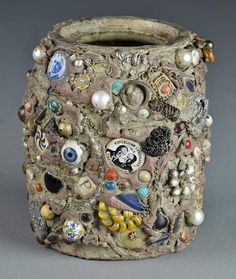 """A Folk Art Memory Jug - Decorated in various materials including Harding and Taft political pins, a watch movement and watch faces, keys, and jewelry beads, over a crazed porcelain vase, measures 6.25""""H. At auction. 1/25/2014 Starting bid $90.00 no bids at this time."""