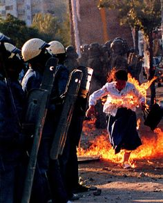 riot police and woman on fire. And no one is helping her.