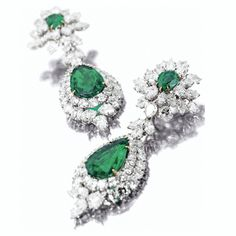 Pair of emerald and diamond pendant-earclips, Harry Winston  Estimate: 200,000 - 250,000 USD  LOT SOLD. 397,000 USD (Hammer Price with Buyer's Premium)  The tops set with 2 pear-shaped emeralds weighing 2.16 and 2.14 carats, framed by clusters of 4 marquise-shaped and 40 pear-shaped diamonds weighing a total of 13.13 carats,  supporting pendants centering 2 pear-shaped emeralds weighing 8.85 and 9.60 carats, framed by 68 round diamonds weighing 11.92 carats and 8 pear-shaped and 4…