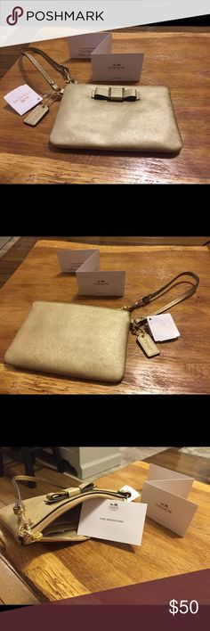 """*NWT* Coach Darcy Gold Wristlet *New* Coach Darcy gold wristlet NWT. New condition. Fits iPhone 6s with room. Petite meets polished in this authentic Coach Darcy Wristlet. In this adorable accessory, a metallic gold Saffiano leather exterior receives a ladylike update through a """"Coach"""" inscribed bow. Meanwhile, a convenient wrist strap and interior sized with just the essentials in mind confirms that this piece offers far more than appearance alone. This Coach item is guaranteed to be…"""