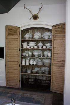 Storage, raw interior shutter doors, white porcelain collection, hung antlers, dark ceiling.