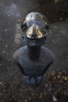 A Giant Glass Raindrop Balances on a Bronze Man's Face in Ukraine
