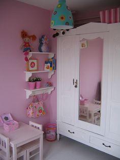 Kinderkamer met roze wanden en een wit geschilderde antieke kast.