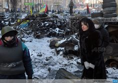 UKRAINE, Kiev : A woman stands near an anti-government barricade in the center of Kiev on January 30, 2014. AFP PHOTO/ SERGEI SUPINSKY