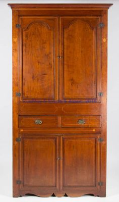 "SOUTHERN INLAID CHERRY CORNER CUPBOARD, one-piece construction, the upper section having applied cove-molded cornice over two hinged fielded-tombstone-panel doors concealing two fixed shelves, waist fitted with two short drawers retaining likely original oval stamped-brass pulls, the lower section with two hinged fielded-panel doors concealing a single fixed shelf, the whole raised on a scrolled cut-out…Probably Virginia, Tennessee, or Kentucky. First quarter 19th century. 88"" H, 23"" corner."