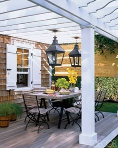Pergola with huge lanterns. cedar shake siding and a table for entertaining. I <3 it!