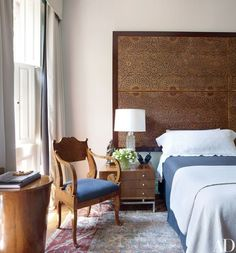 Duffy's headboard is crafted from 19th-century Moroccan ceiling panels, and the chair upholstery and bed skirt are of a Kravet wool; the circa-1825 Russian armchair is from Bernd Goeckler Antiques | archdigest.com