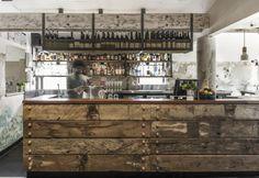 Un lungo bancone corre al centro della sala del pub australiano The Nelson, da poco inaugurato a St. Kilda, Melbourne. Per realizzarlo lo studio Techne Architecture + Interior Design ha utilizzato legno recuperato nei porti vicini