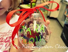 """This is what me made for our """"Christmas Secrets"""" for the parents...  first, we made the Christmas light banners with their names on them.  I took pictures of them holding the banners in front of our class tree and got them printed.  Trimmed them down, stuck them inside plastic ornaments.  The kiddos wrote their name and the year on the ornament with a paint pen.  Simple, and neat...  the kids were so excited about them."""