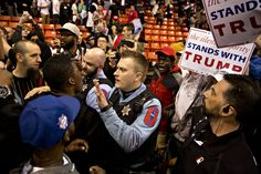 A police officer attempts to calm an attendee at a Donald Trump campaign event Friday in Chicago after the event was cancelled amid clashes between protesters and Trump supporters.