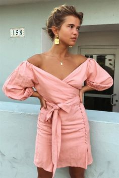 The flattering Tenerife Dress is made from a lightweight cotton fabric in a blush hue. It is an off shoulder style and features puff sleeves, a wrap bodice, cutout at waist and twin pleat and button detailing at front of skirt. Pair with a rattan bag and tan slides! An exclusive Sabo Luxe x Matilda Djerf collaboration.