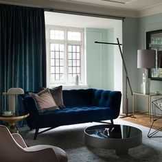 Pale green and blue velvet living room | Decorating | housetohome.co.uk | A luxurious velvet curtain defines this traditional living room, giving it a warm cocooning feel when closed, while a midnight-blue sofa and hints of gold add glamour.
