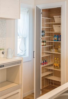 Narrow shelves along the inside wall add extra storage in a small pantry closet.