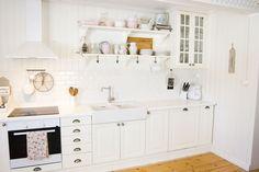 Vitt lantligt kök med öppna hyllor
