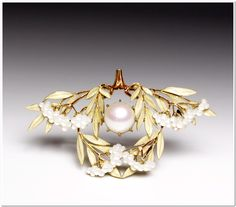A large pale pink pearl is surrounded by leaves and fruit of laurel extending from a short central stalk. The branches are enameled brown and the leaves are covered with thin white, translucent enamel. The clusters of fruit are carved of white mother-of-pearl. René Lalique (French, 1860-1945) (Artist) ca. 1903