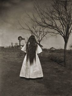 Take on the Skillet Ranch near Lubbock, Texas circa 1910.  Portrait of very long hair, woman in white.