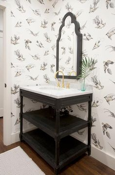 Black and white powder room boasts walls clad in Cole & Son Tropical Birds Frontier Wallpaper lined with a black arched mirror over a black tiered washstand, Restoration Hardware Black Weathered Oak Single Washstand, topped with carrera marble fitted with an oval sink and a gold gooseneck faucet.
