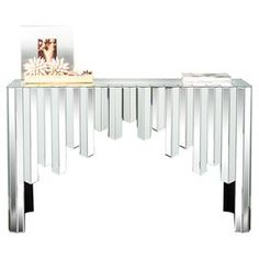 "Wood and glass console table with mirrored panels and a cascading apron.  Product: Console tableConstruction Material: Wood and mirrored glassColor: SilverDimensions: 33"" H x 57"" W x 56"" D"