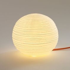 L'utilisation d'une porcelaine structurée complète d'un aspect très doux la forme ronde de cettelampe a poser Balléditée par la maison anversoiseSerax. Cette Lampe designen porcelaine est parfaite dans un salon ou enlampe de chevet. Les stries horizontales et le fil électrique gainé de orange réhaussent la sobriété de cette sphère blanche en porcelaine.